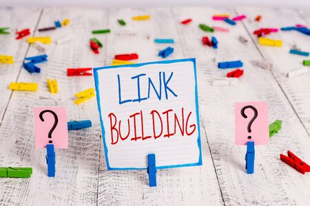 Conceptual hand writing showing Link Building. Concept meaning SEO Term Exchange Links Acquire Hyperlinks Indexed Crumbling sheet with paper clips placed on the wooden table