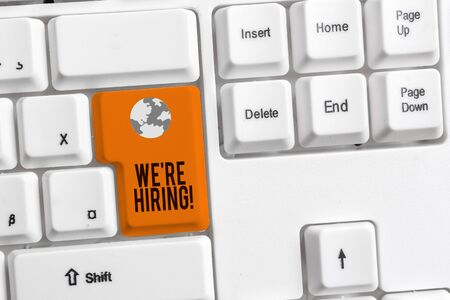 Writing note showing We Re Hiring. Business concept for process of reviewing applications and finding candidates White pc keyboard with note paper above the white background