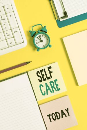 Conceptual hand writing showing Self Care. Concept meaning the practice of taking action to improve one s is own health Crumpled white paper on table clock mobile and pc keyboard