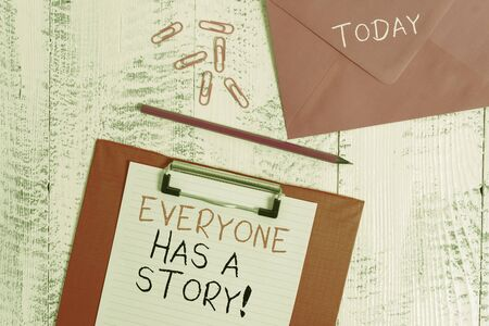 Conceptual hand writing showing Everyone Has A Story. Concept meaning account of past events in someones life or career Colored clipboard paper sheet pencil clips wooden background