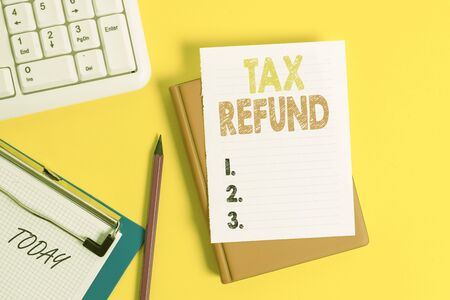 Writing note showing Tax Refund. Business concept for refund on tax when the tax liability is less than the tax paid Pile of empty papers with copy space on the table Imagens
