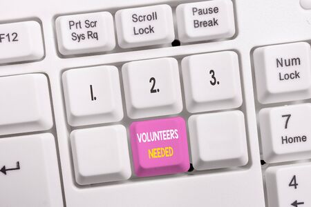 Conceptual hand writing showing Volunteers Needed. Concept meaning need work or help for organization without being paid White pc keyboard with note paper above the white background
