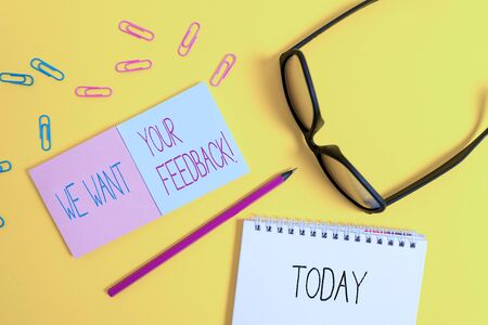 Text sign showing We Want Your Feedback. Business photo showcasing criticism given someone say can be done for improvement Square blank sticky notepads pencil clips eyeglasses yolk color background