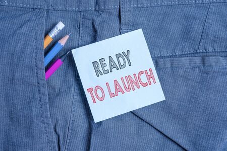 Handwriting text Ready To Launch. Conceptual photo an event to celebrate or introduce something new to market Writing equipment and blue note paper inside pocket of man work trousers