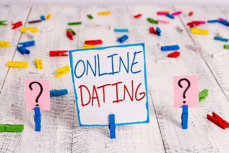 Conceptual hand writing showing Online Dating. Concept meaning Searching Matching Relationships eDating Video Chatting Crumbling sheet with paper clips placed on the wooden table Фото со стока - 130020003
