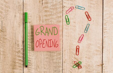 Word writing text Grand Opening. Business photo showcasing Ribbon Cutting New Business First Official Day Launching Pastel colour note paper placed next to stationary above the wooden table