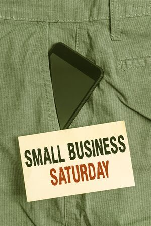 Word writing text Small Business Saturday. Business photo showcasing American shopping holiday held during the Saturday Smartphone device inside formal work trousers front pocket near note paper 版權商用圖片