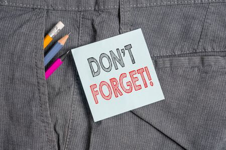 Handwriting text Don T Forget. Conceptual photo used to remind someone about an important fact or detail Writing equipment and blue note paper inside pocket of man work trousers