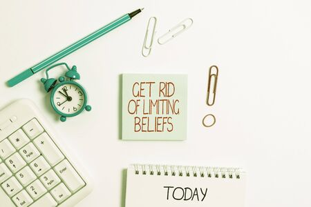 Writing note showing Get Rid Of Limiting Beliefs. Business concept for remove negative beliefs and think positively Copy space on empty note paper with clock and pencil on the table