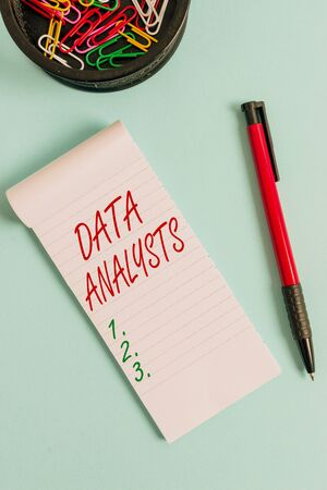 Writing note showing Data Analysts. Business concept for Programmer Design and Create Report Identifies patterns Notebook and stationary with mouse above pastel backdrop