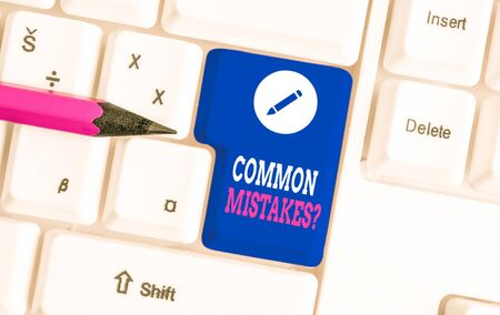 Writing note showing Common Mistakes Question. Business concept for repeat act or judgement misguided making something wrong White pc keyboard with note paper above the white background