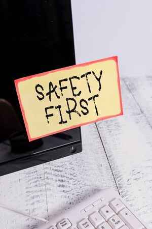 Word writing text Safety First. Business photo showcasing used to say that the most important thing is to be safe Notation paper taped to black computer monitor screen near white keyboard 스톡 콘텐츠