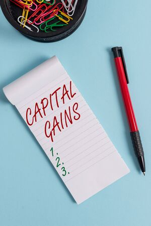 Writing note showing Capital Gains. Business concept for Bonds Shares Stocks Profit Income Tax Investment Funds Notebook and stationary with mouse above pastel backdrop