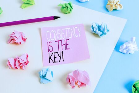 Writing note showing Consistency Is The Key. Business concept for by Breaking Bad Habits and Forming Good Ones Colored crumpled papers empty reminder blue yellow clothespin