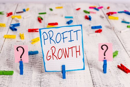 Conceptual hand writing showing Profit Growth. Concept meaning Objectives Interrelation of Overall Sales Market Shares Crumbling sheet with paper clips placed on the wooden table