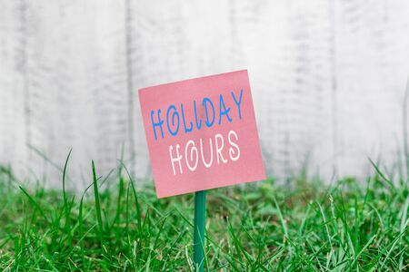 Writing note showing Holiday Hours. Business concept for employee receives twice their normal pay for all hours Plain paper attached to stick and placed in the grassy land