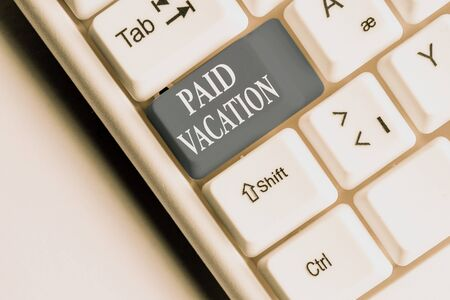 Text sign showing Paid Vacation. Business photo text Sabbatical Weekend Off Holiday Time Off Benefits White pc keyboard with empty note paper above white background key copy space 스톡 콘텐츠