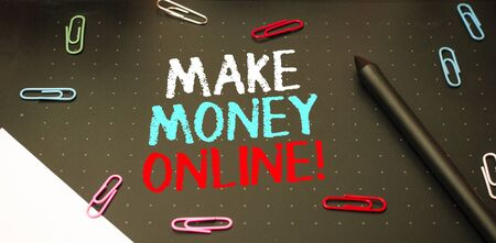 Writing note showing Make Money Online. Business concept for making profit using internet like freelancing or marketing Scissors and writing equipments plus math book above textured backdrop