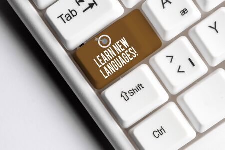 Text sign showing Learn New Languages. Business photo showcasing developing ability to communicate in foreign lang White pc keyboard with empty note paper above white background key copy space
