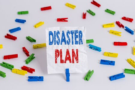 Text sign showing Disaster Plan. Business photo showcasing Respond to Emergency Preparedness Survival and First Aid Kit Colored clothespin papers empty reminder white floor background office 스톡 콘텐츠