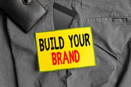 Conceptual hand writing showing Build Your Brand. Concept meaning enhancing brand equity using advertising campaigns Smartphone device inside trousers front pocket with wallet