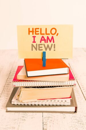 Conceptual hand writing showing Hello I Am New. Concept meaning introducing oneself in a group as fresh worker or student pile stacked books notebook pin color reminder white wooden