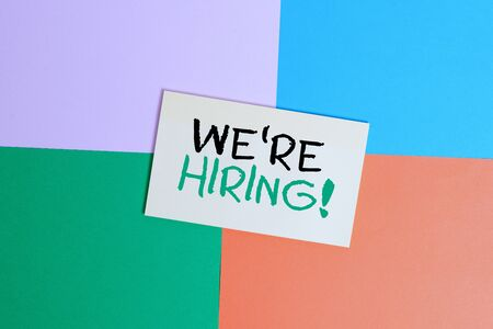 Text sign showing We Re Hiring. Business photo text process of reviewing applications and finding candidates Office appliance colorful square desk study supplies empty paper sticker