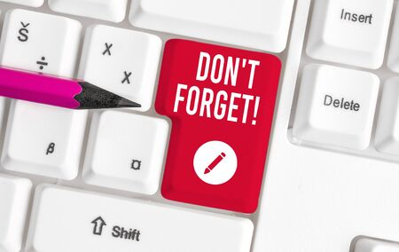 Writing note showing Don T Forget. Business concept for used to remind someone about an important fact or detail White pc keyboard with note paper above the white background