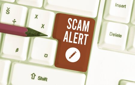 Writing note showing Scam Alert. Business concept for unsolicited email that claims the prospect of a bargain White pc keyboard with note paper above the white background Stock Photo - 129854139