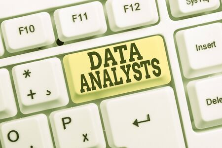 Conceptual hand writing showing Data Analysts. Concept meaning Programmer Design and Create Report Identifies patterns White pc keyboard with note paper above the white background