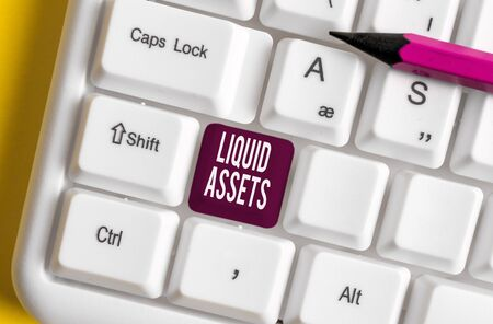 Handwriting text writing Liquid Assets. Conceptual photo Cash and Bank Balances Market Liquidity Deferred Stock White pc keyboard with empty note paper above white background key copy space