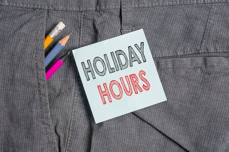Handwriting text Holiday Hours. Conceptual photo employee receives twice their normal pay for all hours Writing equipment and blue note paper inside pocket of man work trousers Reklamní fotografie