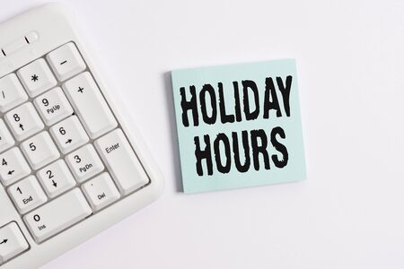 Word writing text Holiday Hours. Business photo showcasing employee receives twice their normal pay for all hours White pc keyboard with empty note paper above white background