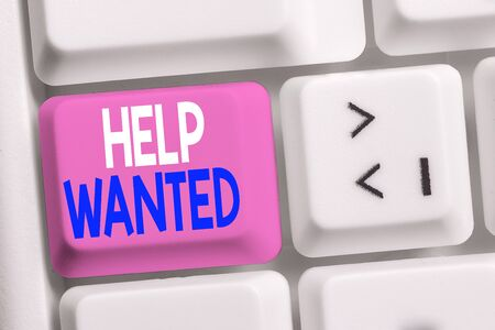 Handwriting text writing Help Wanted. Conceptual photo An ad in the paper an employer places to find a new employee White pc keyboard with empty note paper above white background key copy space 스톡 콘텐츠