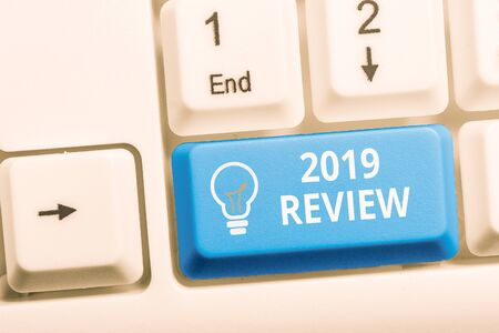 Writing note showing 2019 Review. Business concept for New trends and prospects in tourism or services for 2019 Keyboard with note paper on white background key copy space