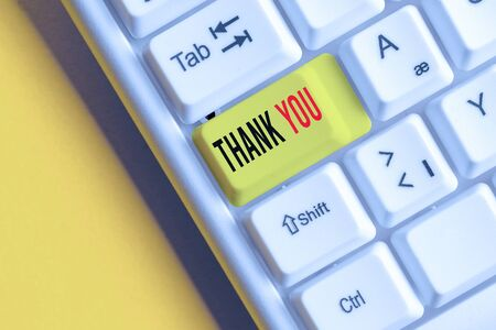 Handwriting text writing Thank You. Conceptual photo a polite expression used when acknowledging a gift or service White pc keyboard with empty note paper above white background key copy space