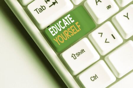 Handwriting text Educate Yourself. Conceptual photo prepare oneself or someone in a particular area or subject White pc keyboard with empty note paper above white background key copy space Stock Photo
