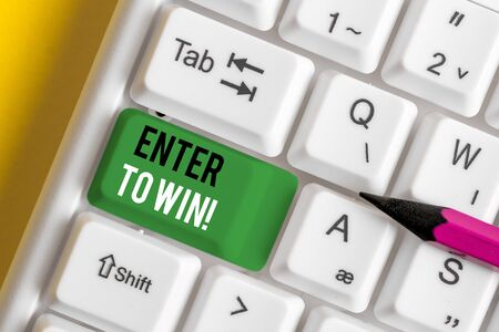 Writing note showing Enter To Win. Business concept for exchanging something value for prize chance winning prize White pc keyboard with note paper above the white background Фото со стока