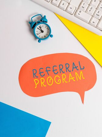 Handwriting text writing Referral Program. Conceptual photo employees are rewarded for introducing suitable recruits Flat lay with copy space on bubble paper clock and paper clips Stock Photo