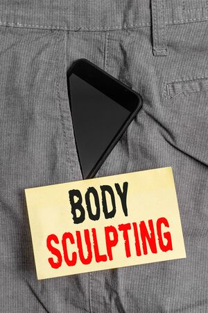 Word writing text Body Sculpting. Business photo showcasing activity of increasing the body s is visible muscle tone Smartphone device inside formal work trousers front pocket near note paper