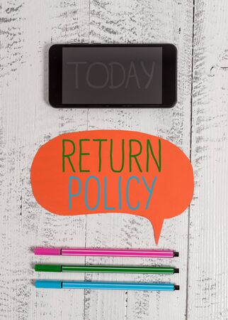 Writing note showing Return Policy. Business concept for Tax Reimbursement Retail Terms and Conditions on Purchase Smartphone cell pens blank colored speech bubble wooden background