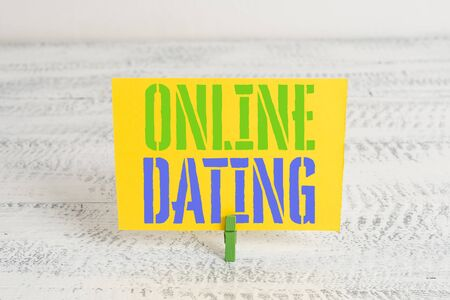 Text sign showing Online Dating. Business photo showcasing Searching Matching Relationships eDating Video Chatting Green clothespin white wood background colored paper reminder office supply