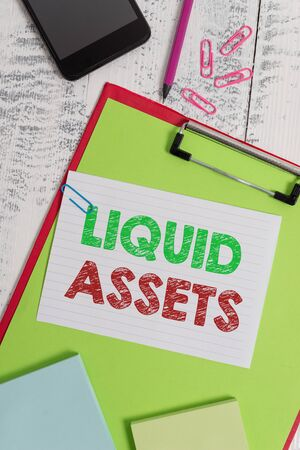 Word writing text Liquid Assets. Business photo showcasing Cash and Bank Balances Market Liquidity Deferred Stock Clipboard sheet pencil smartphone note clips notepads wooden background