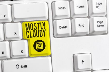 Handwriting text Mostly Cloudy. Conceptual photo Shadowy Vaporous Foggy Fluffy Nebulous Clouds Skyscape White pc keyboard with empty note paper above white background key copy space Stok Fotoğraf
