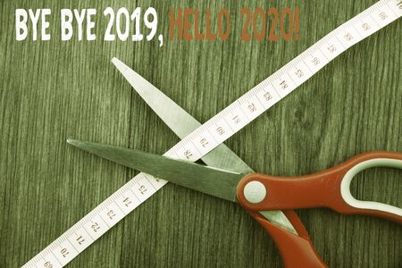 Word writing text Bye Bye 2019 Hello 2020. Business photo showcasing saying goodbye to last year and welcoming another good one Front view wooden background scissors cutting through tape measuring diet Imagens