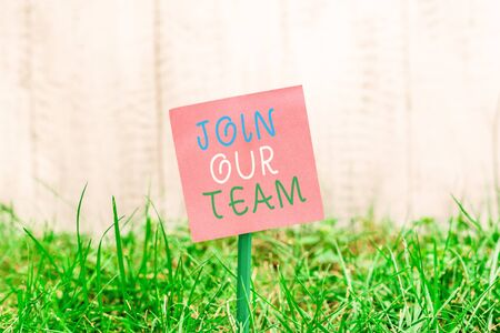 Writing note showing Join Our Team. Business concept for inviting someone to join in your local group or company Plain paper attached to stick and placed in the grassy land 写真素材