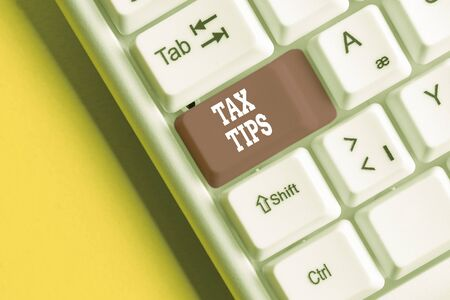 Conceptual hand writing showing Tax Tips. Concept meaning compulsory contribution to state revenue levied by government White pc keyboard with note paper above the white background Stok Fotoğraf