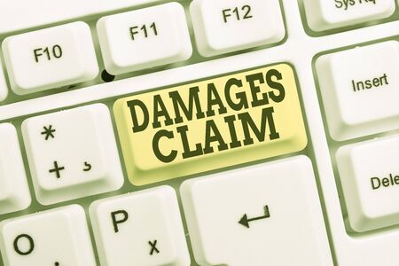 Conceptual hand writing showing Damages Claim. Concept meaning Deanalysisd Compensation Litigate Insurance File Suit White pc keyboard with note paper above the white background
