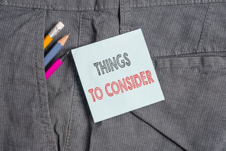 Handwriting text Things To Consider. Conceptual photo think about carefully especially in making decisions Writing equipment and blue note paper inside pocket of man work trousers Stok Fotoğraf - 129853811