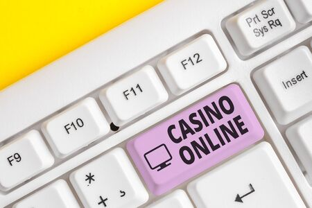 Writing note showing Casino Online. Business concept for Computer Poker Game Gamble Royal Bet Lotto High Stakes White pc keyboard with note paper above the white background 写真素材 - 129853786